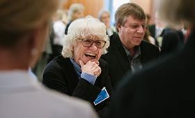 Lachende ältere Frau beim World Café
