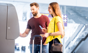 Ein junger Mann und eine junge Frau stehen mit Koffern an einem Geldautomaten an einem Bahnhof und heben Geld ab