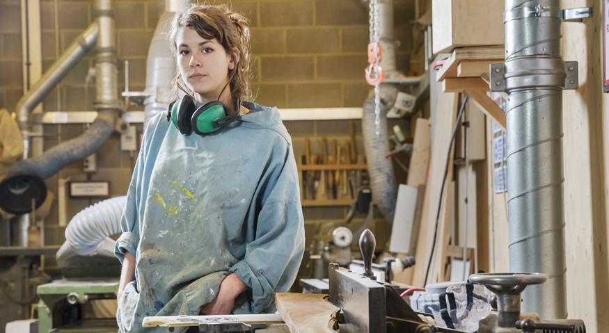 Eine junge Frau steht in Arbeitskleidung und Gehörschutz um den Hals in einer Werkstatt
