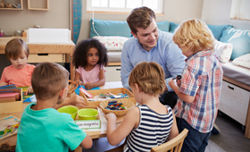 Erzieher mit Kindern an einem Tisch in einer Kindertageseinrichtung