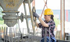 Bauarbeiterin auf Baustelle beim Betongießen