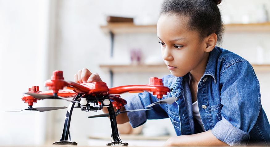 Ein Mädchen in Grundschulalter spielt in ihrem Kinderzimmer mit einer rot-schwarzen Drohne