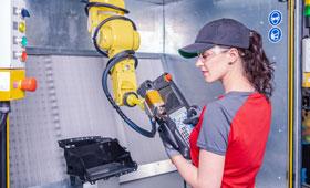 Junge Frau bedient in einer Fabrik eine Maschine