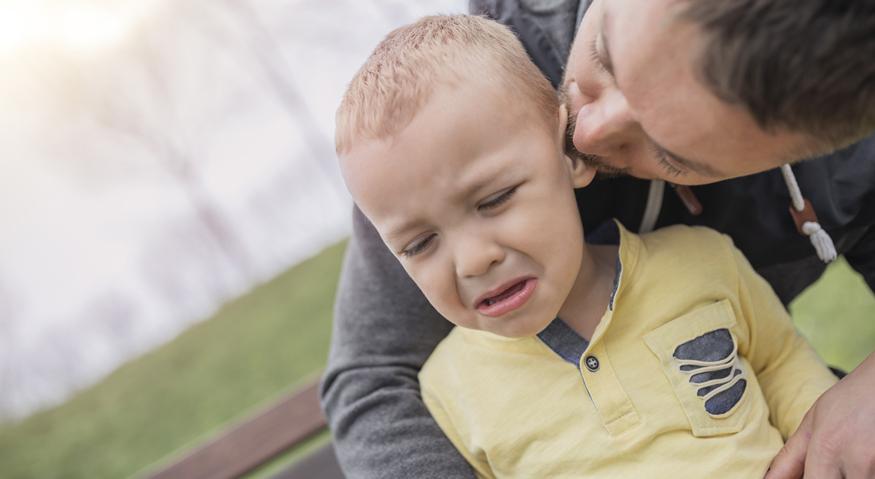 Ein Vater tröstet auf einem Spielplatz seinen kleinen Sohn
