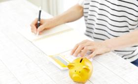 Eine junge Frau – zu sehen sind nur Oberkörper und Unterarme – sitzt mit Notizblock, Stift in der Hand, Taschenrechner und Sparschwein am Schreibtisch