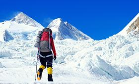 Bergsteigerin vor imposanter Kulisse im Himalaya