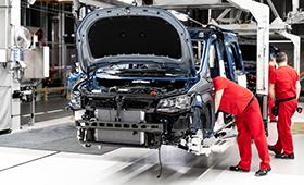 Männer fertigen in einer Fabrik ein Auto