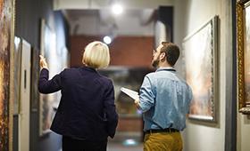 Museumsmitarbeiterin und Museumsmitarbeiter in einer Bildergalerie