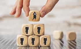 Symbolbild: eine Hand setzt einen Würfel mit einem Frauen-Piktogramm auf 5 Würfel mit Männer-Piktogrammen
