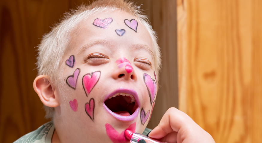 Ein kleiner Junge wird spielerisch mit Lippenstift geschminkt und bekommt Herzchen ins Gesicht gemalt
