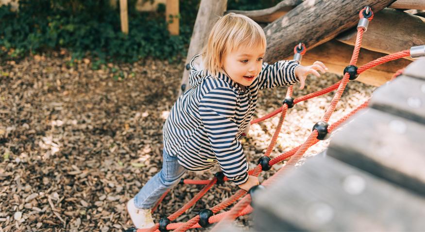 Ein kleines Mädchen klettert auf einem Spielplatz an einem Klettergerüst an den Seilen nach oben
