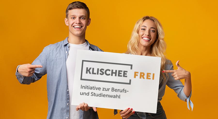 Ein junger Mann und eine junge Frau halten ein Schild mit dem Klischeefrei-Logo und deuten darauf.