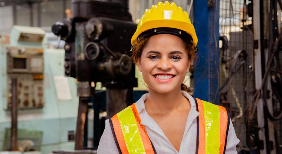 Junge Frau mit Schutzhelm in Fabrikhalle