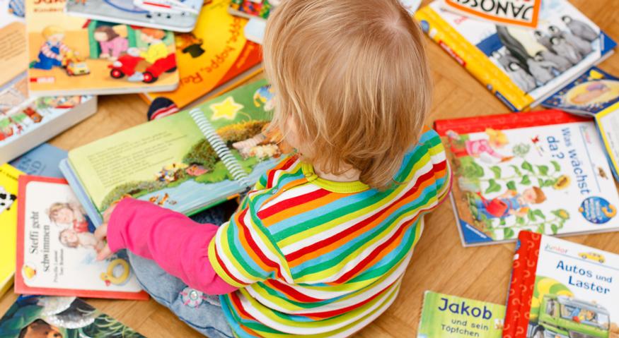Ein Kleinkind sitzt umgeben von Kinderbüchern auf dem Fußboden und schaut sich ein Buch an