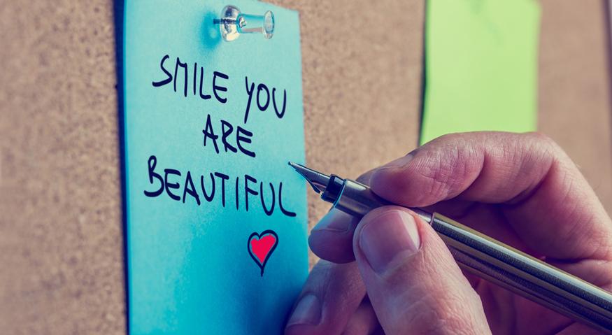 """An eine Korktafel hat jemand ein Post-it mit dem Text """"Smile you are beautiful"""" gepinnt"""