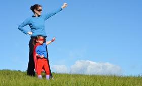 Eine Mutter steht mit ihrer kleinen als Superheldin verkleideten Tochter auf einer Wiese und beide recken ihre Faust
