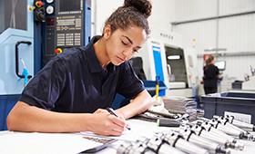 Junge Ingenieurin plant ein Projekt, im Hintergrund eine CNS-Fräsmaschine
