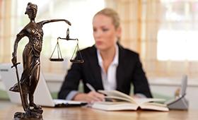 Eine Anwältin sitzt im Büro am Schreibtisch, im Vordergrund steht eine Figur der Justizia