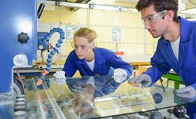 Eine Frau und ein Mann arbeiten mit Schutzbrillen an einem Glasprodukt in einer Fabrik