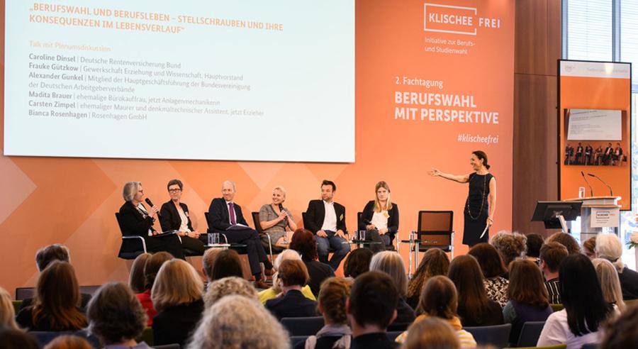 Podiumsteilnehmende, Publikum und Moderatorin, im Hintergrund Programmpunkte auf einer Leinwand