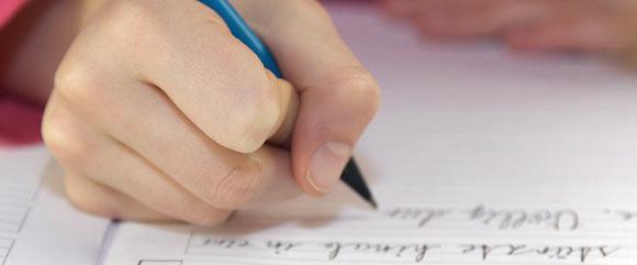 Bildausschnitt: Ein Kind schreibt mit einem blauen Stift in der rechten Hand einen Text.