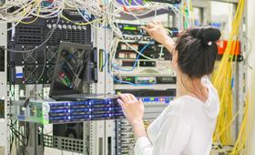 Eine junge Frau arbeitet in einem Serverraum, wo sie im Datencenter Kabel zusammensteckt.