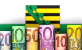 gerollte Euroscheine vor dem Hintergrund der Landesflagge Sachsen