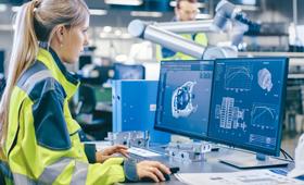 Eine Ingenieurin entwirft in einer Fabrikhalle eine Maschine am Rechner
