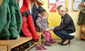 Eine Mutter holt ihr Kind vom Kindergarten ab und zieht es im Flur knieend an