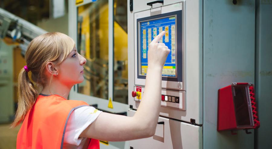 Junge Frau bedient computergesteuerte Maschine in Fertigungshalle