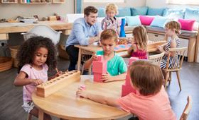 Ein Erzieher in einem Montessori-Kindergarten spielt mit Kindern an einem Tisch