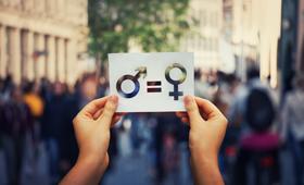 Eine Hand hebt ein Blatt hoch, auf dem die Symbole für Mann und Frau mit einem Ist-Gleich-Zeichen verbunden sind