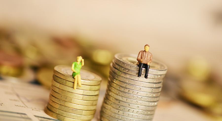 Zwei unterschiedlich hohe Münzstapel mit einer Frauenfigur und einer Männerfigur symbolisieren ungleiche Bezahlung zwischen den Geschlechtern