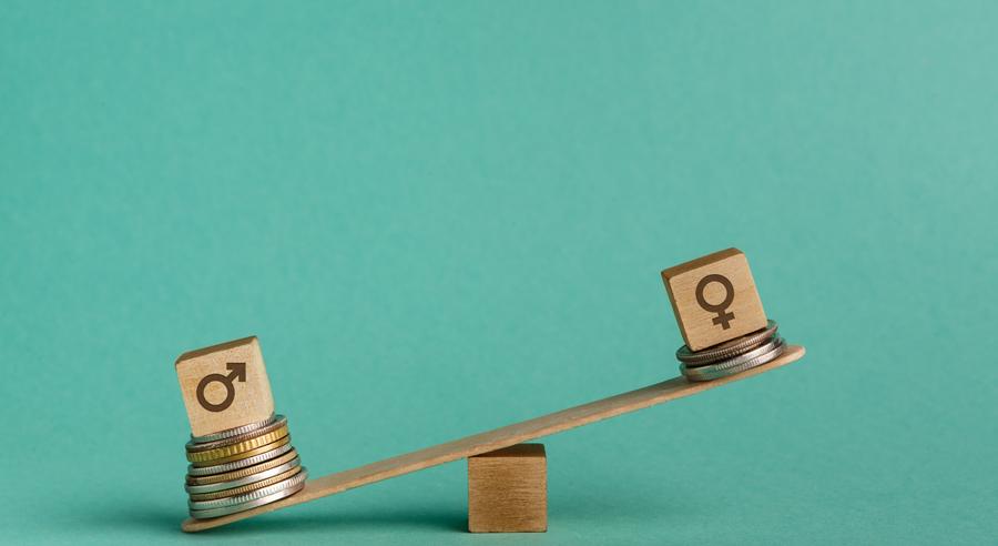 Unterschiedlich hohe Münzstapel auf einer geneigten Wage symbolisieren die Ungleichheit von Einkommen bei Männern und Frauen