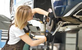 Eine junge Kfz-Mechatronikerin repariert in einer Werkstatt ein Auto