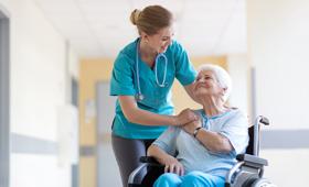 Eine weibliche Pflegekraft kümmert sich um eine ältere Frau im Rollstuhl