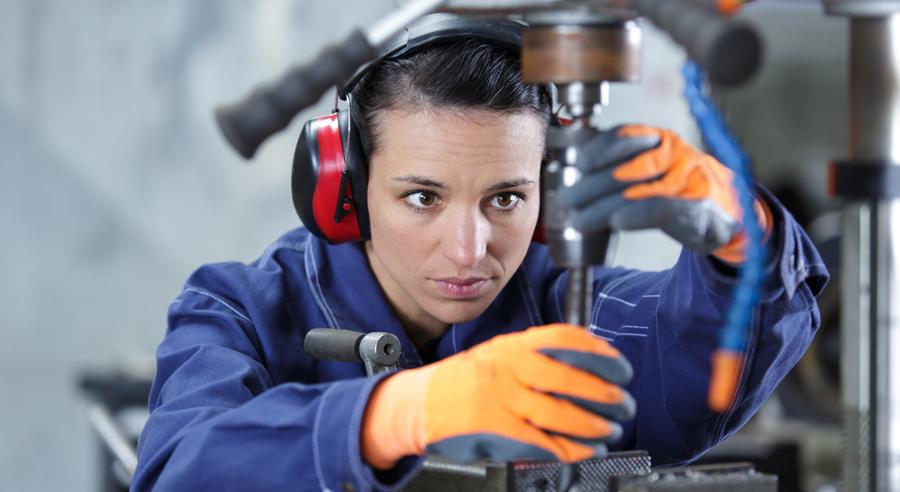Frau arbeitet im Blaumann an einer Fabrikmaschine