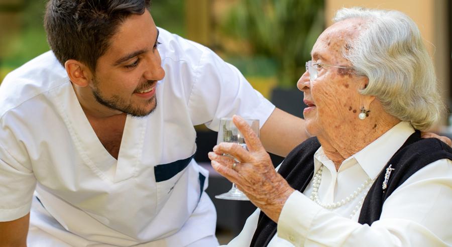 Junger Pfleger assistiert Seniorin