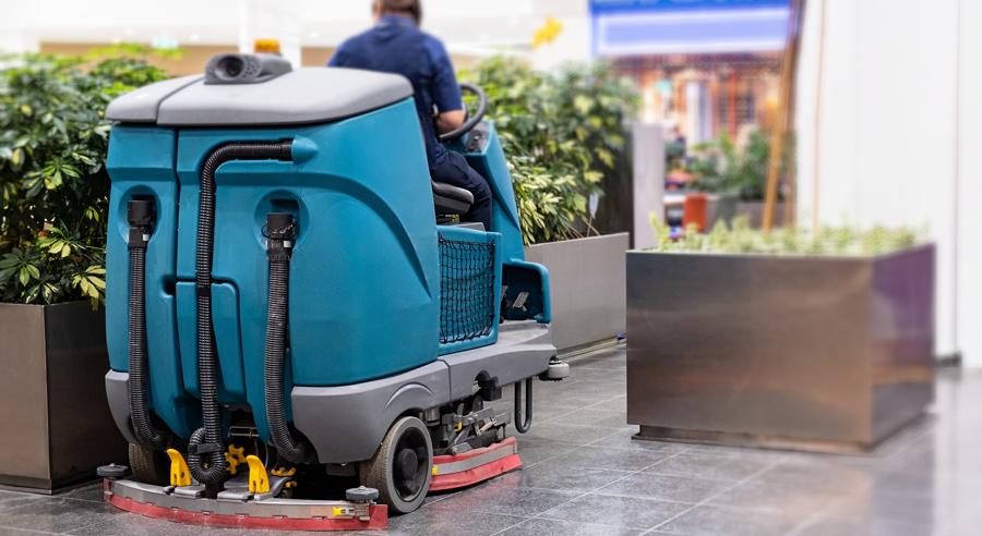 Eine Kehrmaschine mit einer Person fährt durch ein Einkaufszentrum und reinigt den Fußboden