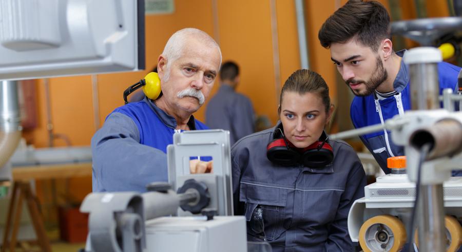 Ein älterer Ausbilder erklärt einem jungen Auszubildenden und einer jungen Auszubildenden die Funktionsweise einer Maschine in einer Fabrik