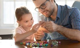 Ein Vater bringt mit seiner Tochter am Tisch sitzend bunte Steinchen an einem Faden an