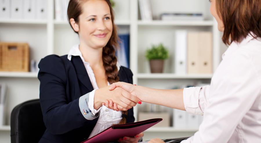 Eine Frau schüttelt einer anderen Frau am Tisch sitzend die Hand nach einem Bewerbungsgespräch
