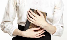 Oberkörper einer Lehrerin in weißer Bluse um die Jahrhundertwende, die Hände halten ein Buch