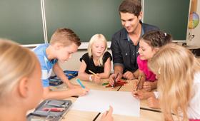 Ein Grundschullehrer sitzt mit Kindern an einem Tisch und zeichnet