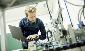 Ingenieur mit Laptop in einer Fabrikhalle beugt sich über eine Maschine