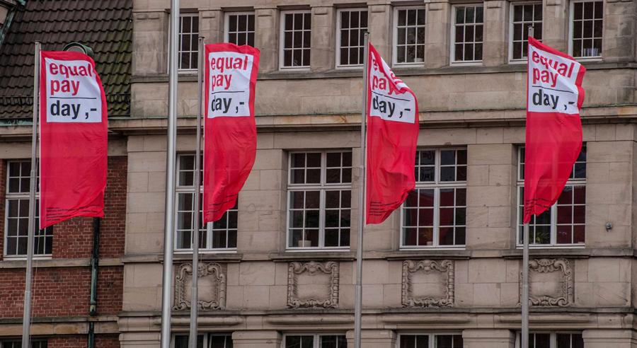 Stuhlreihen mit Taschen des Equal Pay Day über den Lehnen