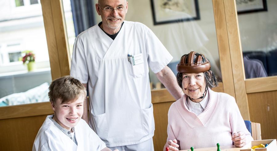 Ein Pfleger und ein Boys'Day-Teilnehmer spielen mit einer Bewohnerin einer Pflegeeinrichtung ein Gesellschaftsspiel