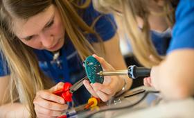 Teilnehmende an einem Girls'Day schrauben an einem elektronischen Kleingerät