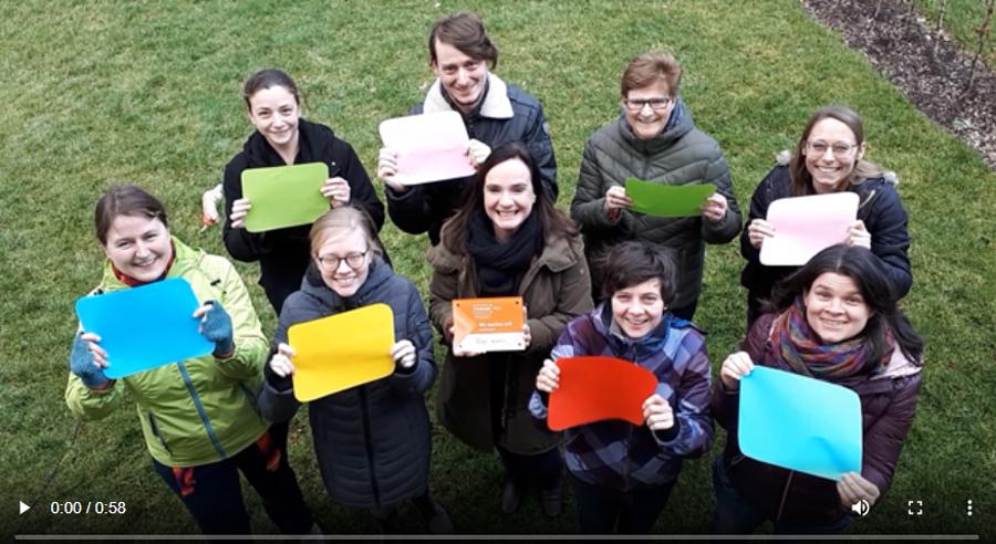 Mitarbeitende der Initiative junge Forscherinnen und Forscher stehen auf einer Wiese und halten farbige Blätter hoch