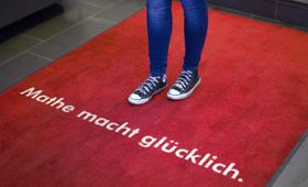 """Die Beine eines Mädchens in Jeans stehen auf einem roten Teppich mit der Aufschrift """"Mathe macht glücklich"""""""